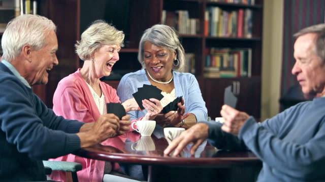 Four seniors drinking coffee, playing card game Four multi-ethnic seniors sitting at a table indoors, drinking coffee and playing a card game. playing card stock videos & royalty-free footage