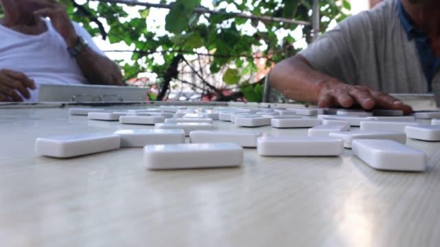 vier senioren mature cuban man spielt domino outdoor patio havanna - havanna stock-videos und b-roll-filmmaterial