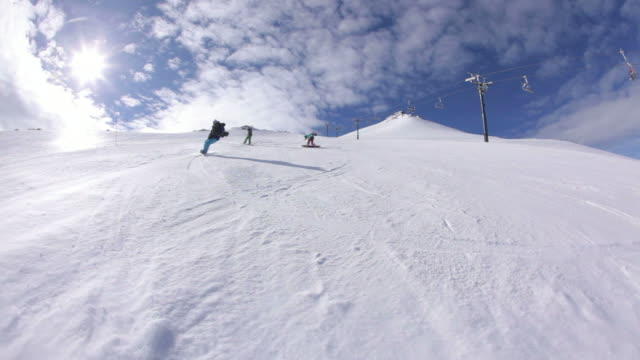 Four snowboarders ride down ski slope video