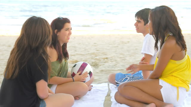 Four teens sit together on the beach video