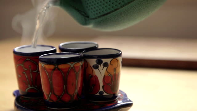 four traditional cups and a green tea chest that poured hot water to them four traditional colorful cups in the front and on focus, in back a green tea chest that a hand take it and poured hot water to the cups daylight savings stock videos & royalty-free footage