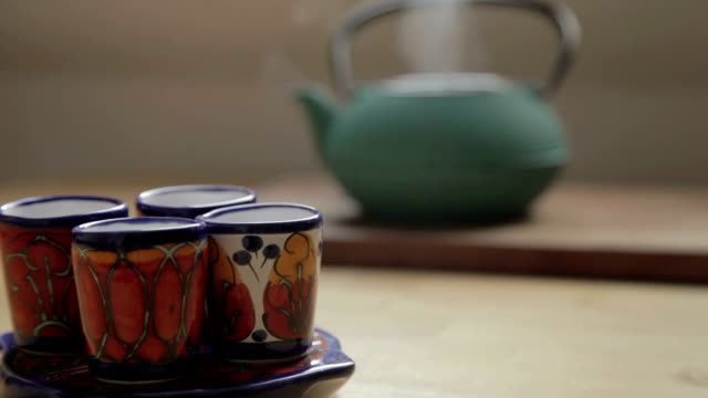 four traditional cups in focus on the front and back a green tea chest, pouring and steam four traditional cups in focus on the front and back a green tea chest, and a coffee pot poured hot water to the tea chest and after put her lid and the coffee pot to the side daylight savings stock videos & royalty-free footage