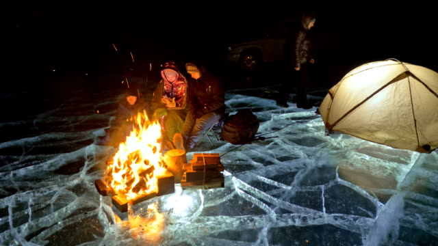 four travelers by fire right on ice at night. campground on ice. tent stands next to fire. people are warming around campfire. photographer in shoots on camera in tripod. - ice on fire video stock e b–roll