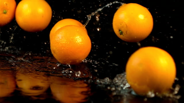 Four videos of falling oranges in real slow motion video