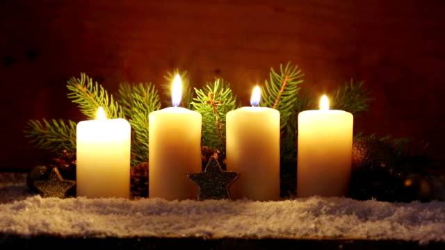 Four white Advent candles with christmas decoration video