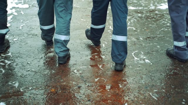 vídeos de stock e filmes b-roll de four workers in a gray uniform with a horizontal white stripe on their pants are walking along the asphalt with wet snow in black boots. - bota