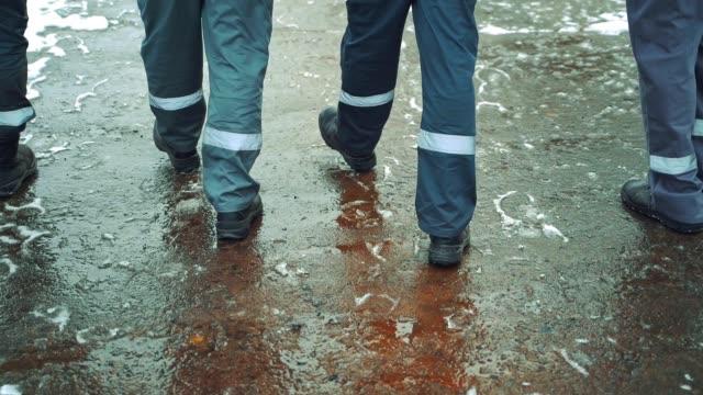 vidéos et rushes de quatre ouvriers dans un uniforme gris avec une rayure blanche horizontale sur leur pantalon marchent le long de l'asphalte avec de la neige mouillée dans des bottes noires. - bottes