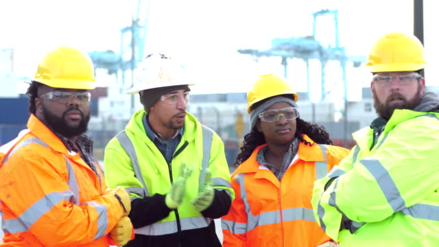 Four workers talking, working at shipping port Four multi-ethnic workers working at a seaport, wearing reflective jackets, hardhats, and safety glasses. The foreman, a mixed race Hispanic man in his 30s, is giving directions to the others. The team includes an African-American woman. In the background are gantry cranes and cargo containers. construction machinery stock videos & royalty-free footage