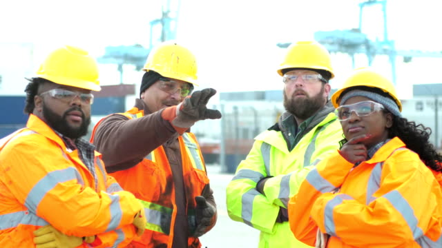 Four workers talking, working at shipping port Four multi-ethnic workers working at a seaport, wearing reflective jackets, hardhats, and safety glasses. The foreman, a mature Hispanic man in his 40s, is giving directions to the others. The team includes an African-American woman. In the background are gantry cranes and cargo containers. occupational safety and health stock videos & royalty-free footage