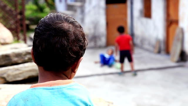 Four year old kid wearing alternative clothes and watching other kids playing together. video
