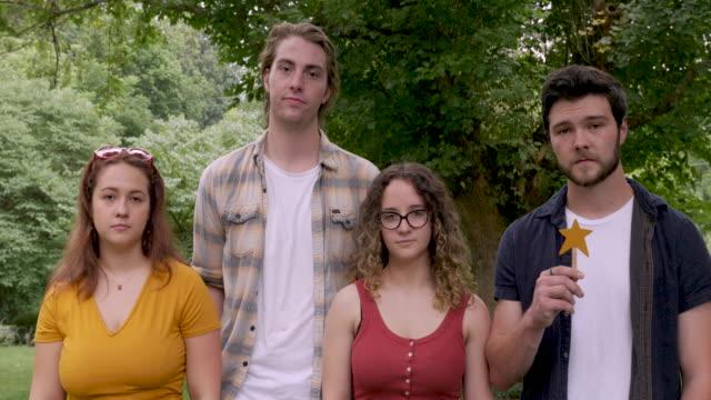 vier junge erwachsene geben eine zwei-sterne-bewertung, die einen durchschnitt oder mittelmäßig bedeutet - feedback stock-videos und b-roll-filmmaterial