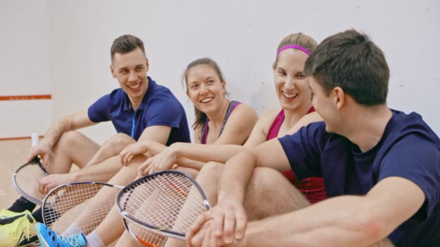 Four young adults sitting in the squash court and talking after the game