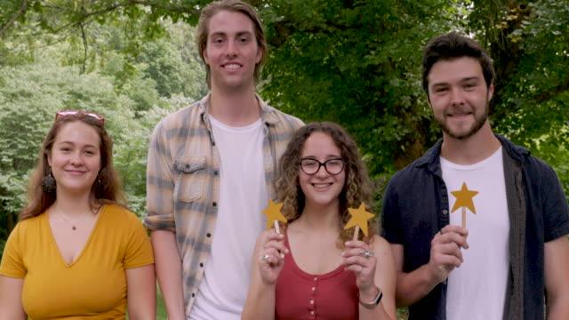 vier junge attraktive erwachsene lächeln, geben eine fünf-sterne-bewertung und einen daumen nach oben - feedback stock-videos und b-roll-filmmaterial