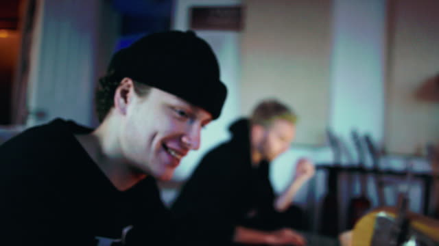 Four Young Men in Their Twenties Hang out while Talking, Working on Their Computers, Playing the Electric Bass Guitar, and Recording Music in a Home Recording Studio (Band)