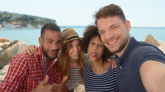 Four young people taking selfies by the sea