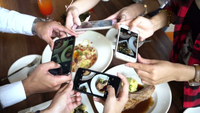 Four young people using a mobile phone and taking photos of spaghetti and food at restaurant