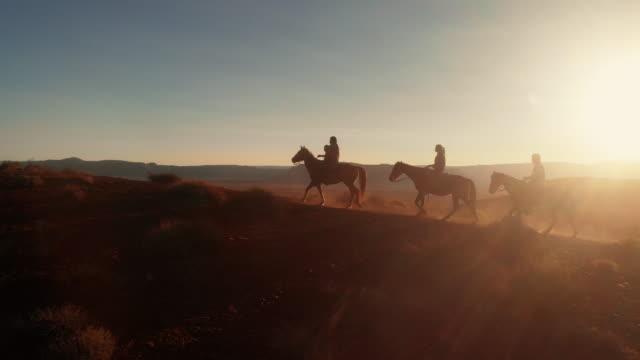 quattro giovani adolescenti e fratelli più piccoli nativi americani navajo in sella ai loro cavalli bareback nel deserto vicino al monument valley tribal park al crepuscolo in estate - andare a cavallo video stock e b–roll
