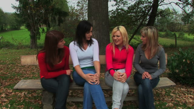 Four young womens siting on bench in nature and talk Four young womens siting on bench in nature and talk cross legged stock videos & royalty-free footage
