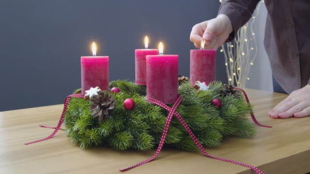 Fourth Sunday of Advent - a young woman is lighting the fourth candle of the advent wreath video