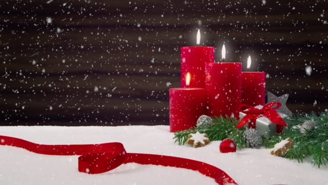 Fourth Sunday of Advent - Beautiful snowfall in front of a Christmas decoration arrangement on a snowy table in front of a wooden background video