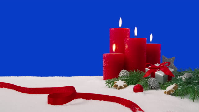 Fourth Sunday of Advent - Christmas decoration arrangement on a snowy table in front of a blue screen A Christmas decoration arrangement with four candles, fir branches, a wrapped gift, scattered decoration elements and a red ribbon on a snowy table in front of a blue screen. All candles are lit, which are burning with beautiful flames. weihnachten stock videos & royalty-free footage