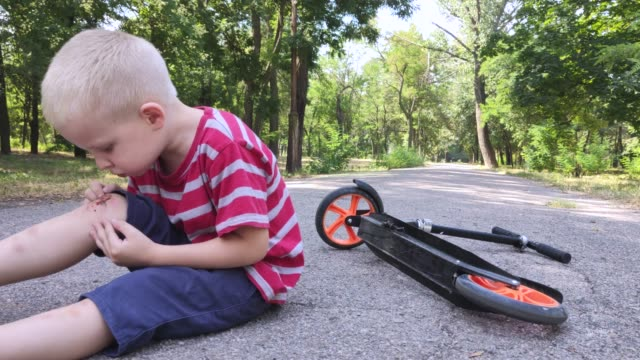 a four-year-old child fell off a scooter and injured his knee. the child cries, rubs his knee and blows on it. the concept of sloppy driving and parental carelessness. - rana filmów i materiałów b-roll