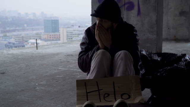 Fozen homeless rubs his hands to warm up video