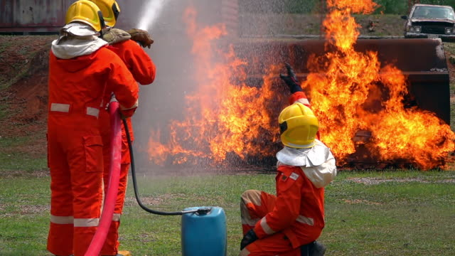 FHD 250 fps slow motion wide shot of firefighter in fire suit on safety rescue duty with crackle fire flames in burning oil truck. Three firemen using water extinguisher from a hose for fighting a fire inside burning premises.
