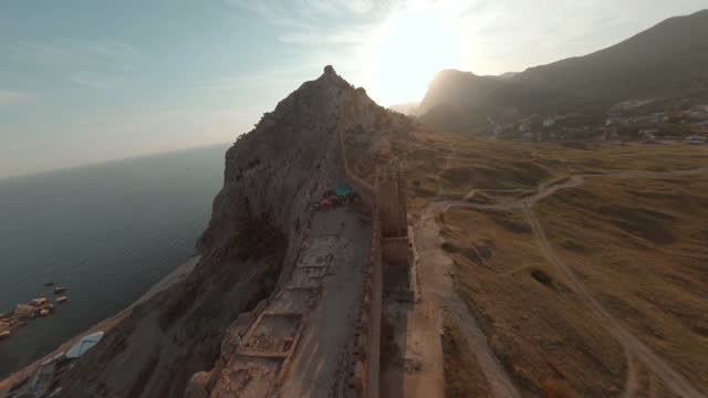 Fpv cinematic sport drone shooting Sudak city sunset landscape and ancient fortress along mountain. Aerial view antique walls and towers Genoese fortress on picturesque Black Sea landscape