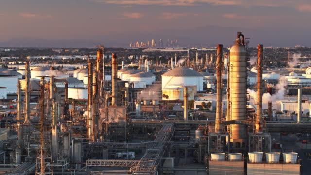 stockvideo's en b-roll-footage met fractionele destillatie tower in olieraffinaderij bij zonsondergang - luchtfoto - chemische fabriek