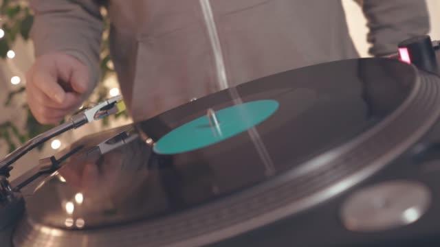 vídeos y material grabado en eventos de stock de fragmento de una placa de vinilo rotativa en tocadiscos dj con el telón de fondo de luces de fiesta brillantes. el dj se acerca al reproductor de música y pone el lápiz óptico con la aguja. vista lateral - disco audio analógico