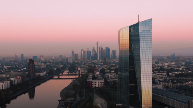 frankfurt ecb skyline aerial shot at early sunrise reflecting sun - francoforte sul meno video stock e b–roll