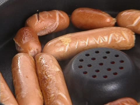 Frankfurter sausage being backed in pan video