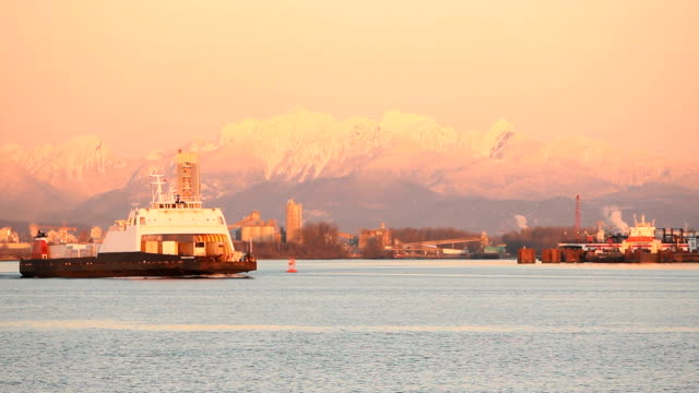 Fraser River Truck Barge Moving Down Stream At dusk, a barge full truck trailers travels on an industrial section of the Fraser River near Vancouver, British Columbia, Canada. The BC Coast Mountains rise in the background. fraser river stock videos & royalty-free footage