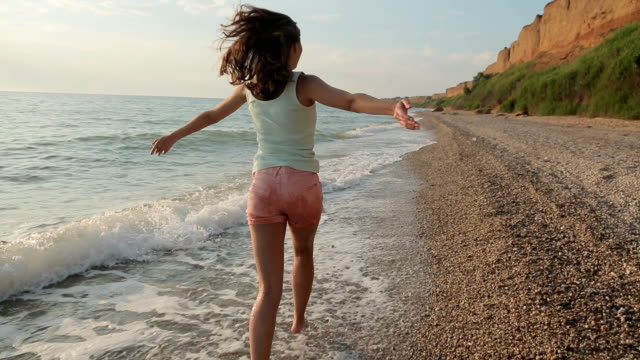 Free girl running barefoot on the water along a deserted beach in the summer video