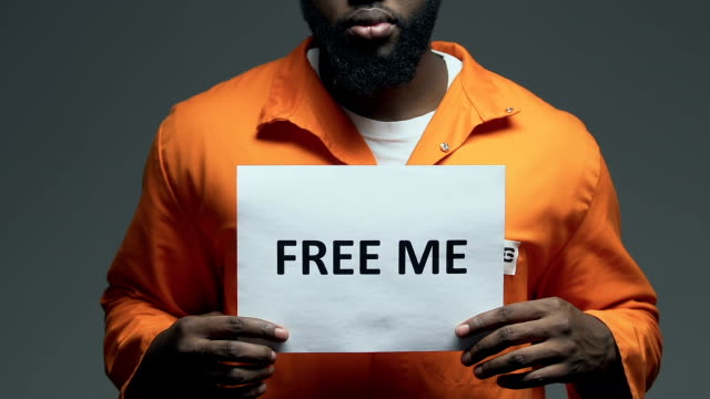 Free me phrase on cardboard in hands of Afro-American prisoner, amnesty asking Free me phrase on cardboard in hands of Afro-American prisoner, amnesty asking civil rights stock videos & royalty-free footage
