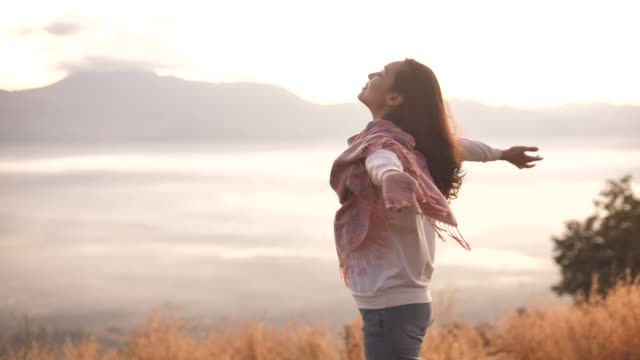 freedom asian woman open arms in sunlight on mountain - modlić się filmów i materiałów b-roll