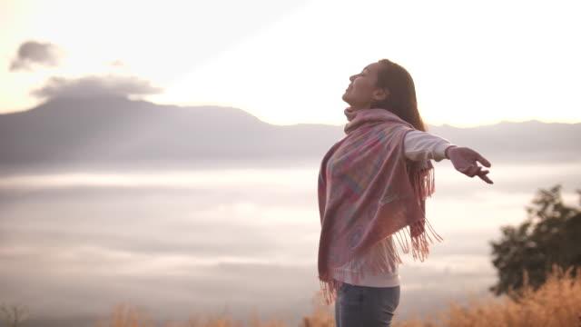 自由アジアの女性立って、山の上に腕を上げ、夕日の眺めを楽しむ - バックパッカー点の映像素材/bロール