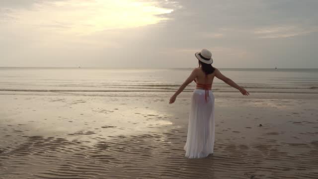 vidéos et rushes de femme de liberté dans le bikini marchant avec des bras levés sur la plage de mer - bras humain