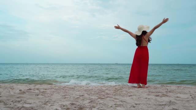 vidéos et rushes de femme de liberté marchant avec des bras levés sur la plage de mer avec le coup de vent - bras humain
