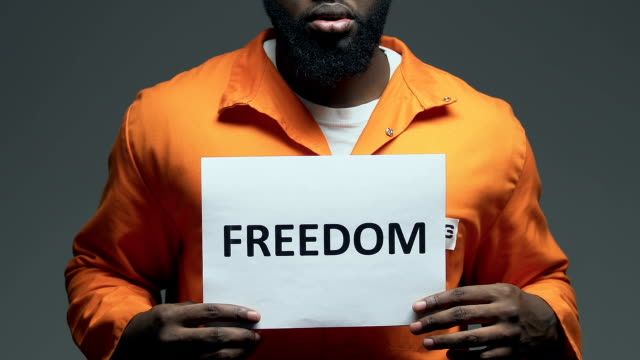 Freedom word on cardboard in hands of Afro-American prisoner, asking for amnesty Freedom word on cardboard in hands of Afro-American prisoner, asking for amnesty civil rights stock videos & royalty-free footage