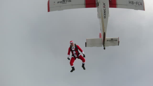 Freefall jumper dressed in santa suit falls towards snowy mountains