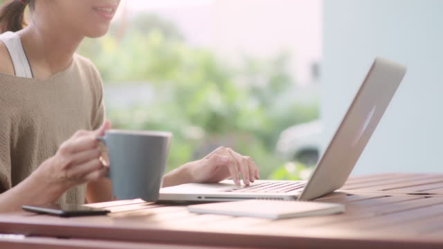 Freelance Asian woman working at home, business female working on laptop and drinking coffee sitting on table in the garden in morning. Lifestyle women working at home concept.