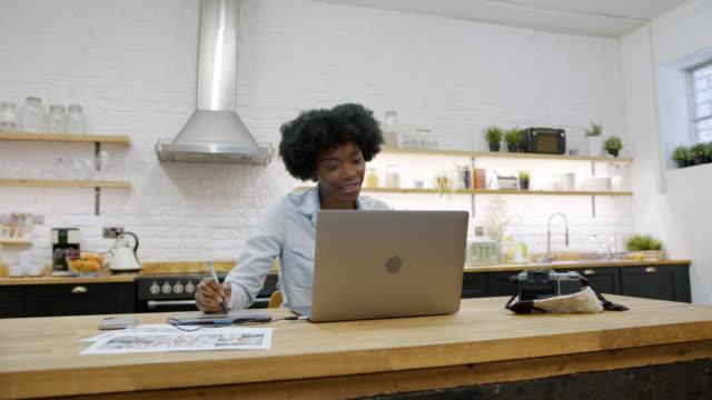 fotografo freelance che modifica le foto a casa sul suo computer portatile sorridendo - designer professionista video stock e b–roll