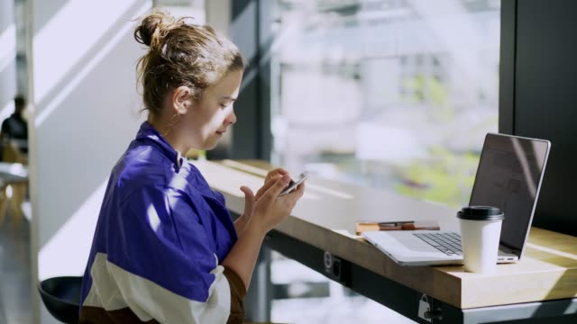 freelancer girl working in public place - banchi scuola video stock e b–roll