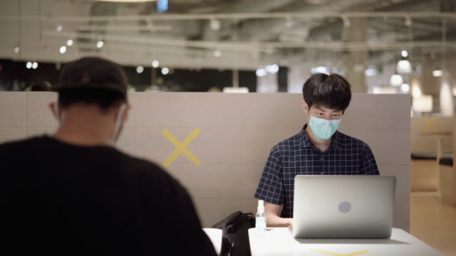 freelancer man using pollution mask for using laptop at coffee shop - new normal video stock e b–roll