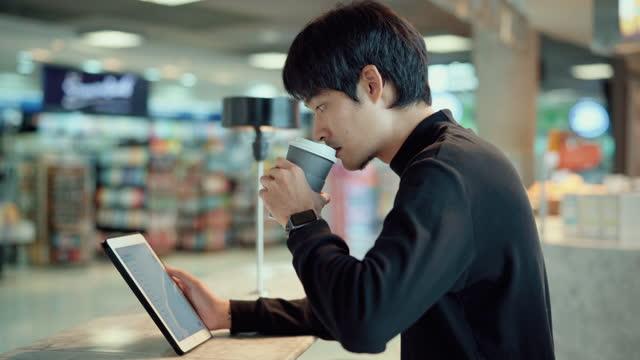 カフェでデジタルタブレットを扱うフリーランサーの男性 - カフェ文化点の映像素材/bロール