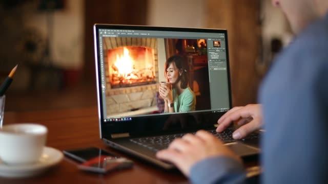 l'uomo ritocco freelance lavora al computer portatile con sofware di fotoritocco. fotografo o designer al lavoro. elaborazione digitale delle immagini. tracciamento e rivelazione di colpi - fotografia immagine video stock e b–roll