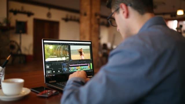 フリーランサーのビデオエディターは、動画編集ソフトウェアとラップトップ コンピューターで動作します。ビデオブログを編集作業でのビデオ撮影ビデオブロガーやブロガー カメラ男。追跡と明らかにショット - 編集者点の映像素材/bロール
