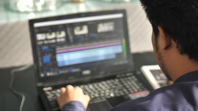 フリーランサーのビデオエディタは、ラップトップで動作します - 編集者点の映像素材/bロール
